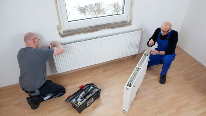 Two technicians substitute an heater