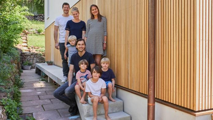 Familie mit kleinen Kindern vor Hauswand