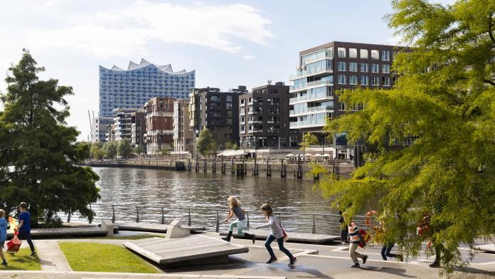 Blick auf zwei spielende Kinder vor dem Hintergrund der Hamburger Hafen-City und der Elbphilharmonie