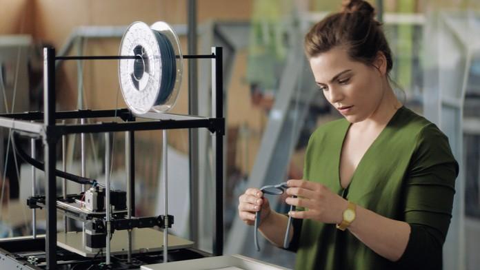 Junge Frau betrachtet einen Brillen-Prototyp