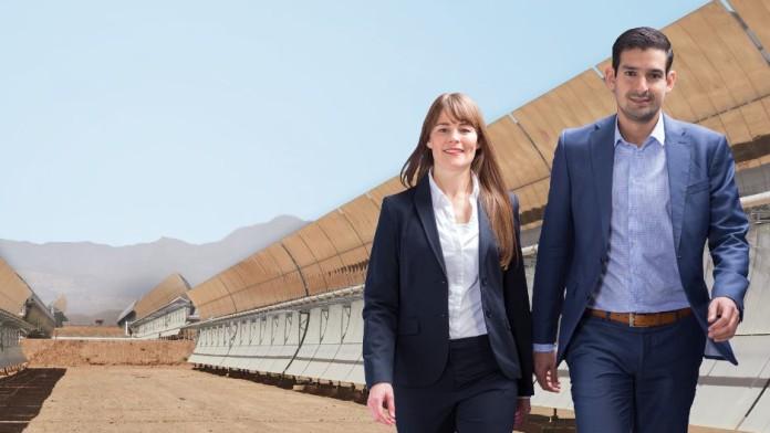 Zwei Mitarbeiter, die das FZ-Projekt Bau eines Solarparks in Marokko betreut haben, laufen dynamisch und smart aussehend durch den Solarpark.