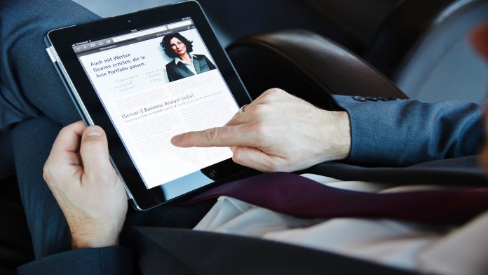 Mann schaut KfW-Stellenausschreibung mit Tablet-PC an.