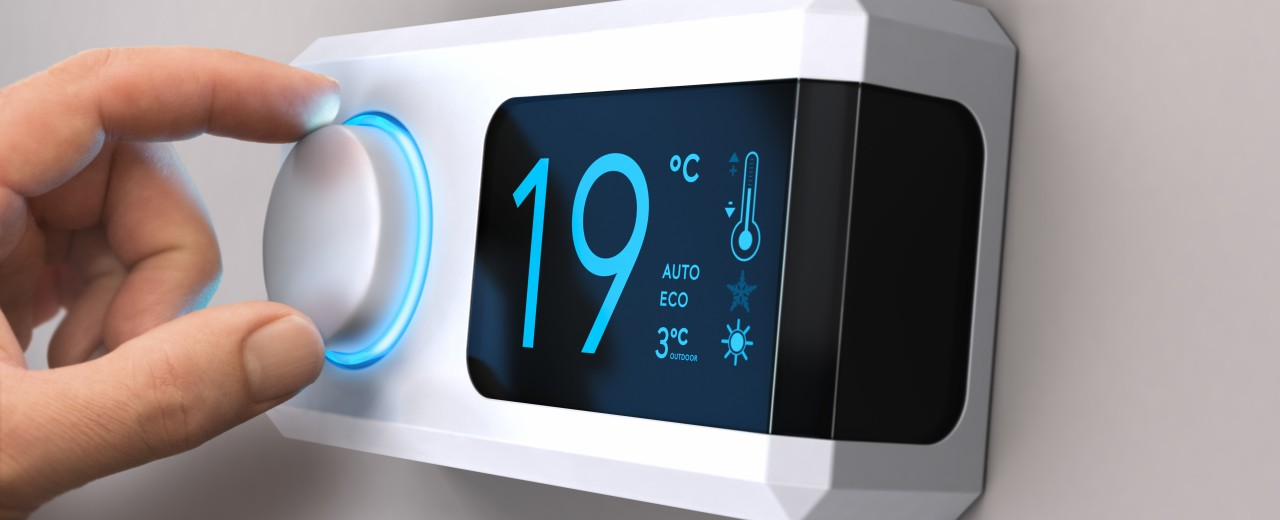 Hand turning a home thermostat knob to set temperature on energy saving mode. celcius units
