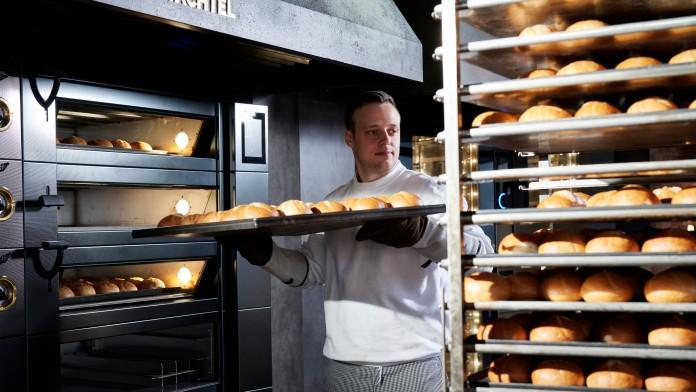 Bäcker zieht ein Blech mit frischen Brötchen aus dem Ofen