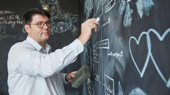 Mann schreibt auf eine Tafel