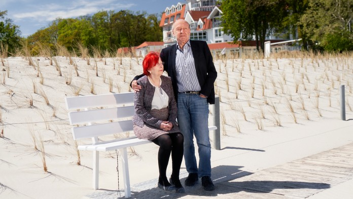 Ehepaar am Strand vor Hotel