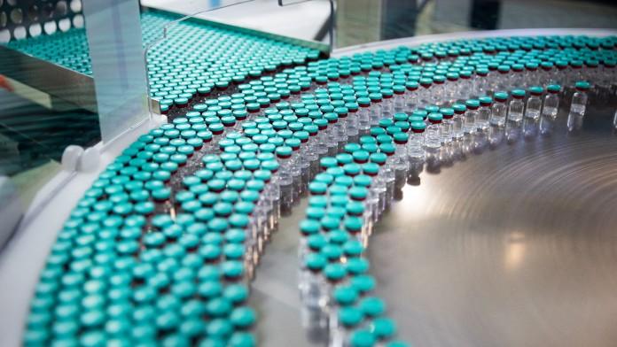 Mehrere kleine Fläschchen mit Impfstoff in einer chemischen Industrie