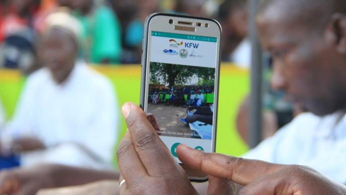 Eine Person filmt oder fotografiert eine Menschenmenge in der Ferne mit seinem Smartphone.