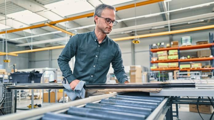 Mitarbeiter begutachtet ein Rohr in der Produktionshalle
