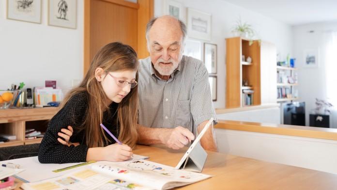 Mädchen und ihr Opa sitzen am Esstisch und machen gemeinsam Hausaufgaben am Tablet