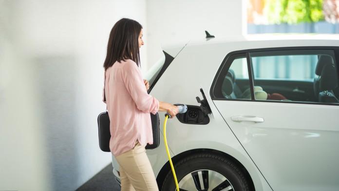 Eine Frau lädt ihr weißes Elektroauto an einer Ladestation auf.