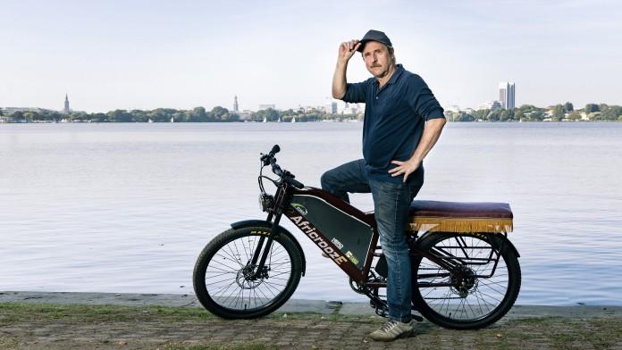 Schauspieler Bjarne Mädel auf dem African E-Bike an der Alster.