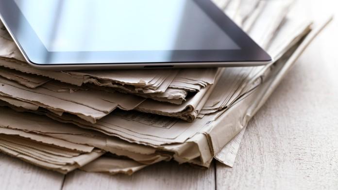 Alte Zeitungen mit Tablet Computer