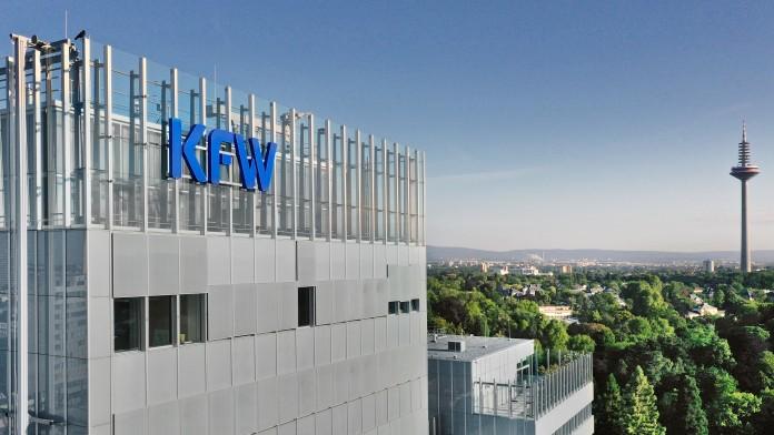 Drohnenaufnahme der KfW-Zentrale Frankfurt. Links im Bild das Haupthaus mit KfW Logo, rechts Ausblick auf den Palmengarten und in der Ferne der Ginnheimer Fernsehturm.