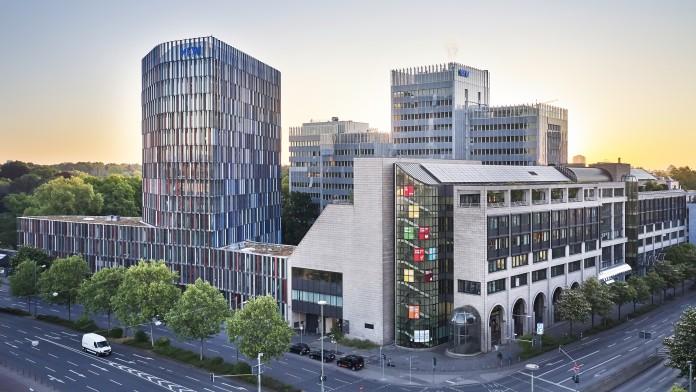 Drohnenaufnahme des KfW Gebäudes in Frankfurt bei Sonnenuntergang. Im Vordergrund eine Straßenkreuzung, links das IPEX Gebäude, rechtes die Nordarkade der KfW, im Hintergrund das Haupthaus der KfW.