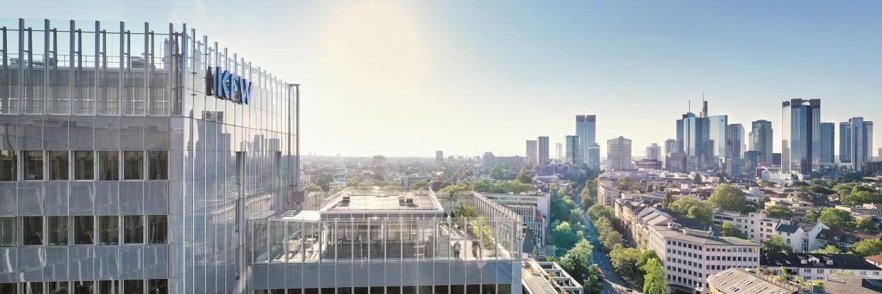 Drohnenaufnahme des KfW Standorts in Frankfurt. Links im Vordergrund das Haupthaus der KfW, rechts im Hintergrund die Skyline. Der Himmel ist wolkenlos, die Sonne scheint.