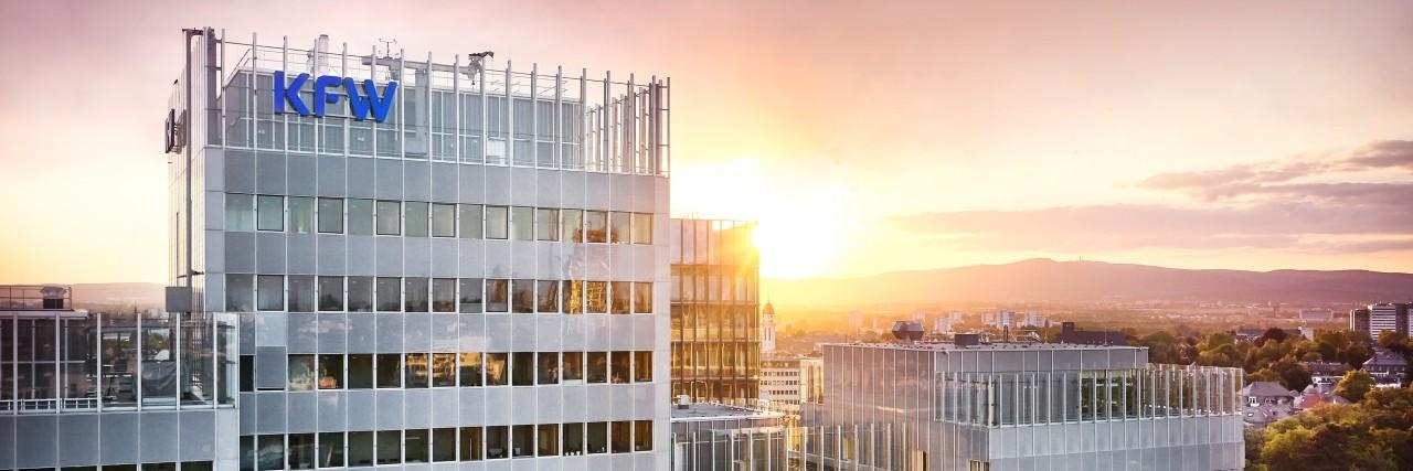 Luftaufnahme des KfW Haupthauses in Frankfurt mit KfW Logo, im Hintergrund ein Sonnenuntergang.