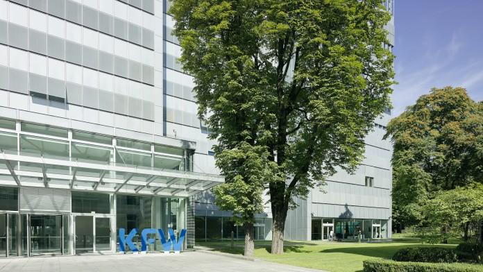 Ausschnitt des Eingangs zum KfW-Haupthaus. Angrenzend wächst ein großer Baum.