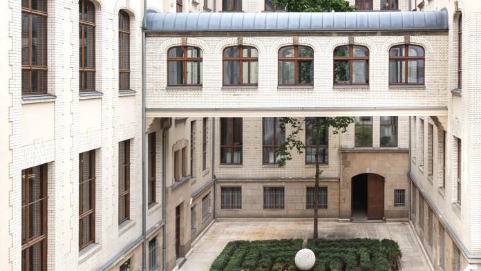 Begrünter Innenhof des KfW Gebäudes Berlin. Ein Durchgang verbindet beide Seiten des ersten Stocks.