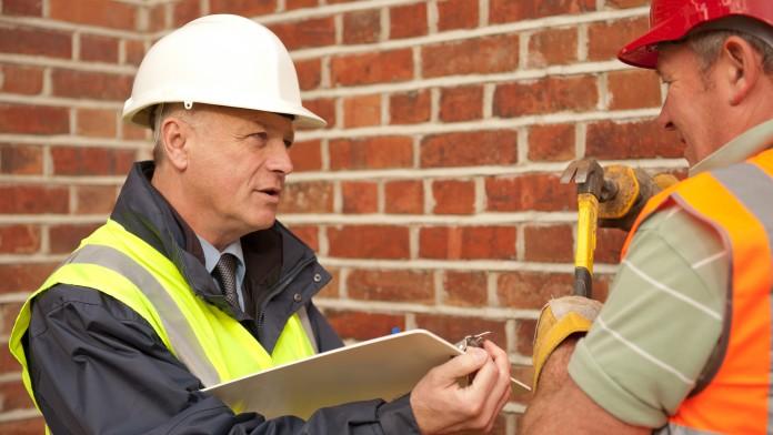 Ein Bauleiter und ein Bauarbeiter vor einer Backsteinwand
