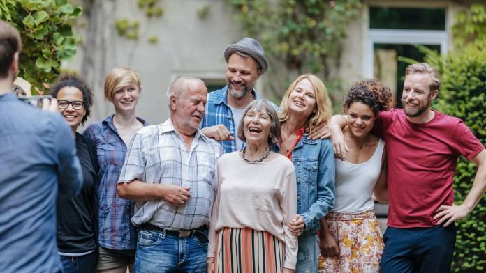 Eine Gruppe von Menschen unterschiedlichen Alters steht vor einem Haus