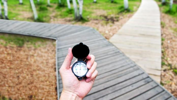 Ein Kompass in einer Hand vor einer Weggabelung