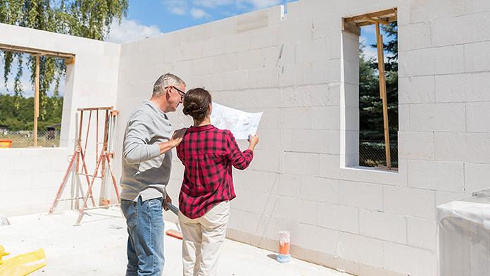Paar steht auf der Baustelle des neuen Hauses