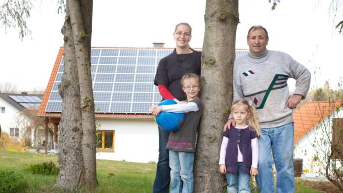 Familie auf einer Wiese vor Ihrem Haus