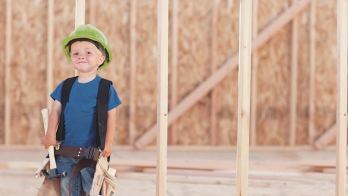 Ein Kleiner Junge mit Schutzhelm und Handwerkergeräten steht vor Holzgerüst