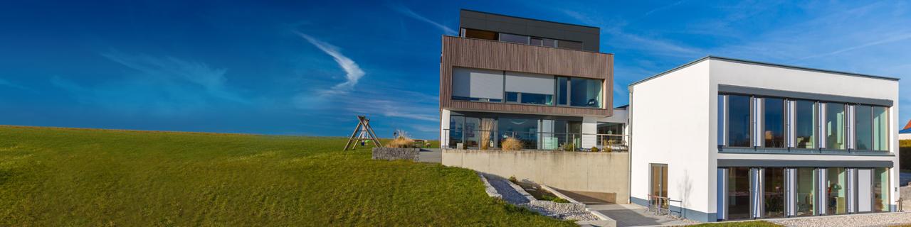Zwei moderne neue Häuser auf einer großen Wiese vor blauem Himmel