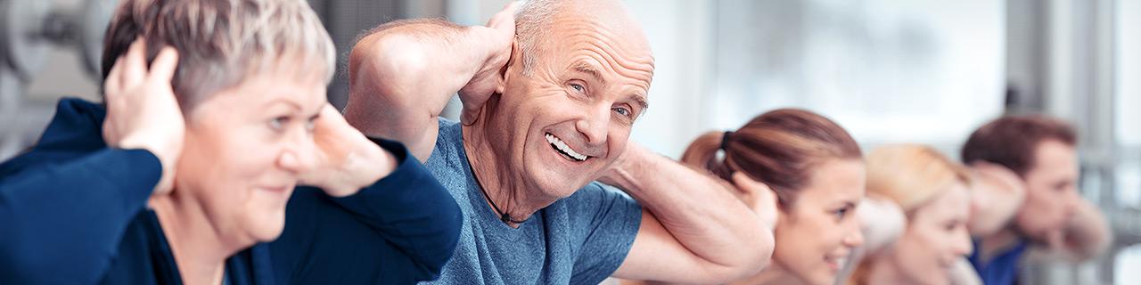 In einer Reihe machen junge und ältere Menschen Sportübungen auf Gymnastikbällen
