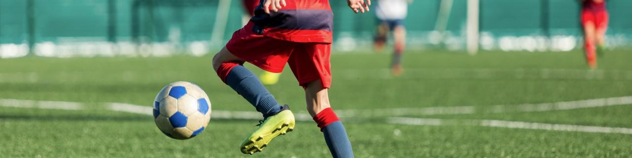 Fussballplatz vor einer Halle, wo ein Junge im Trikot den Ball zum Tor dribbelt