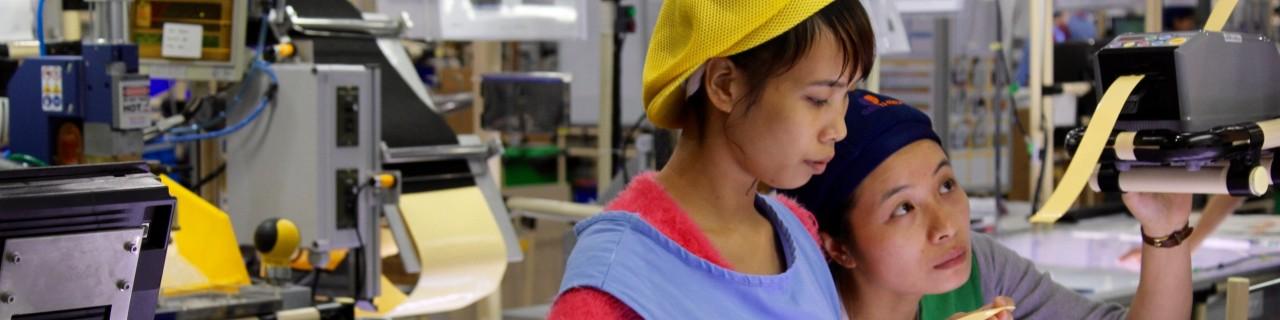 Zwei Arbeiterinnen schauen auf eine Maschine in einer Fabrik