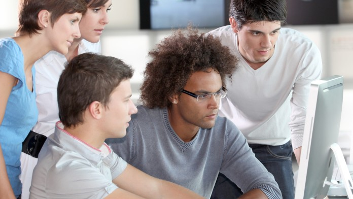Eine Gruppe junger Menschen schaut gemeinsam auf einen Bildschirm