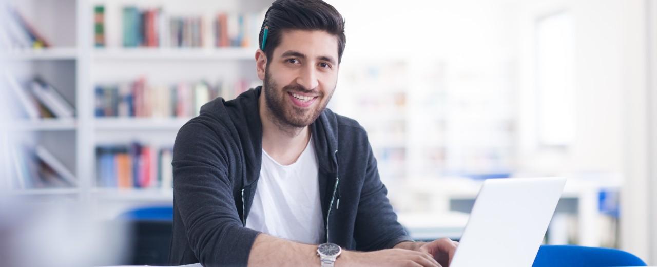 Junger Mann sitzt mit einem Stift hinter dem Ohr vor einem Laptop und lächelt.