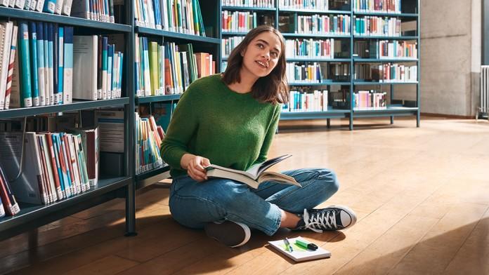 Studentin sitzend zwischen Bücherregalen