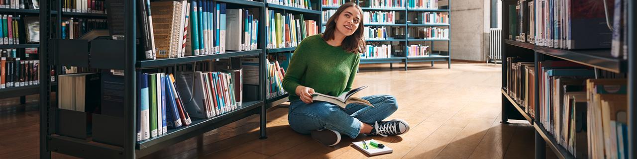 Studentin sitzt auf dem Boden in einer Bibliothek und liest ein Buch