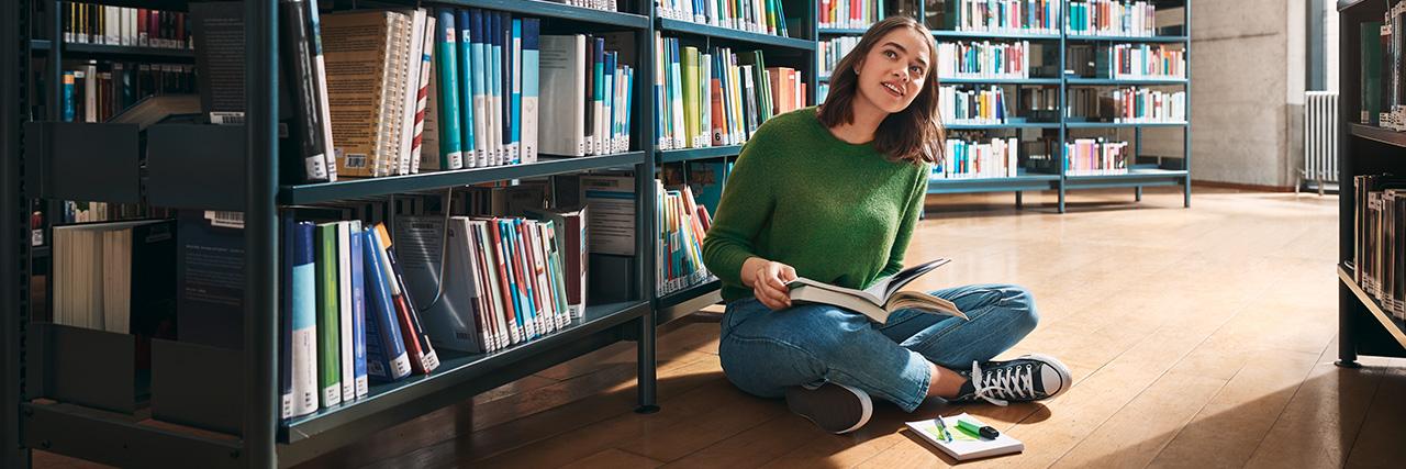 Studentin sitzt auf dem Boden einer Bibliothek und liest ein Buch