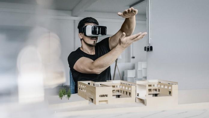 Junger Mann mit Virtual Reality Brille steht vor einem Architekturmodell
