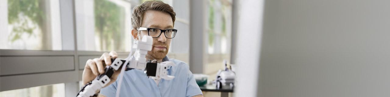 Ein Mann mit Brille zeigt einen Roboterarm