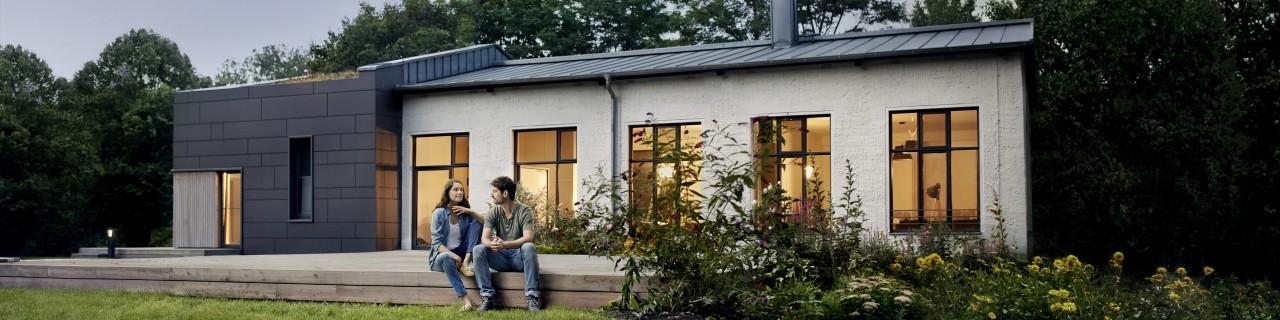 Frau und Mann sitzen auf der Terrasse vor dem sanierten Haus mit Blick in den Garten.