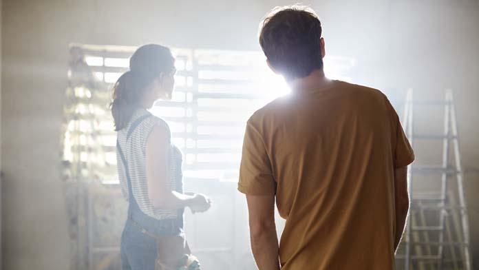 Paar steht in lichtdurchfluteten Raum, in dem gerade die Fenster ausgetauscht werden.