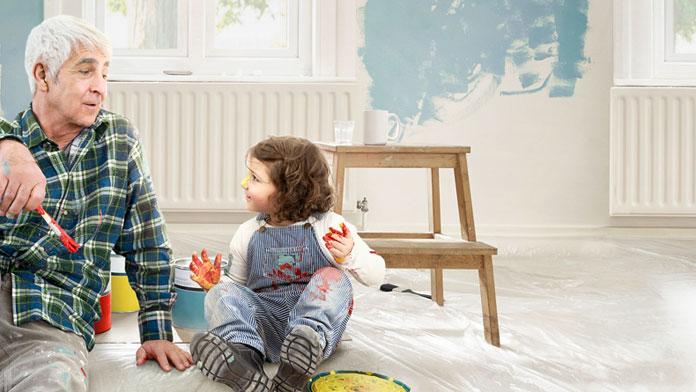 Opa und Enkelin sitzen auf dem Boden und wollen gemeinsam die Wände streichen.