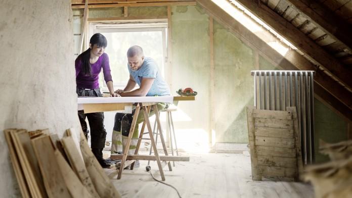 Frau und Mann stehen im Dachgeschoss und schauen sich gemeinsam die Pläne zum Ausbau an.