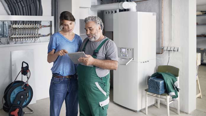 Frau und Handwerker stehen im Keller und schauen auf ein Tablet, im Hintergrund ist die neue Heizung zu sehen.