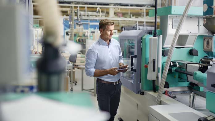 Unternehmer steht mit seinem Tablet in einer Produktionshalle und begutachtet die neue Maschine.