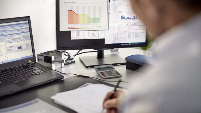 Mann sitzt am Schreibtisch und macht sich Notizen zum Energieverbrauch.