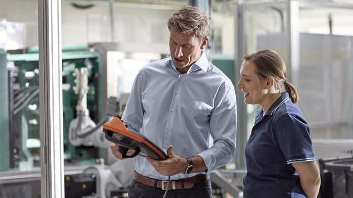 Frau und Mann schauen auf die Fernbedienung der neuen Produktionsmaschine.