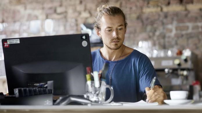 Gründer sitzt am Schreibtisch und macht sich Notizen.