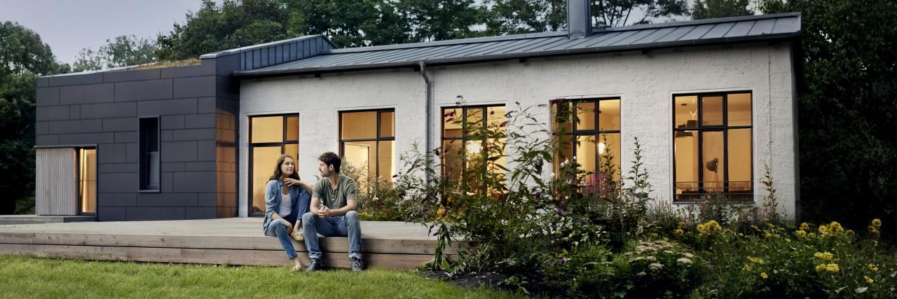 Junges Pärchen sitzt im Garten ihres modernen Einfamilienhauses